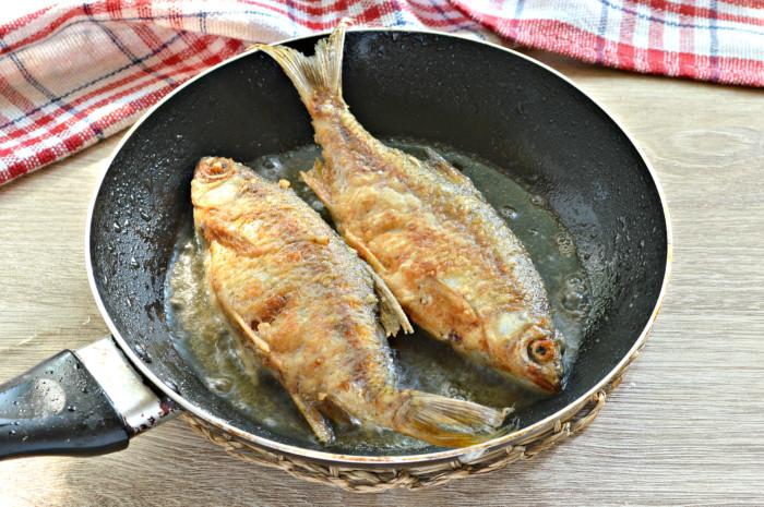 Мелкая жареная речная рыба на сковороде